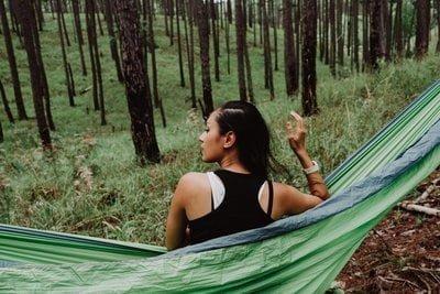Femme de dos dans un hamac en toile face à une forêt