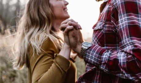 Couple face à face qui se tient les mains