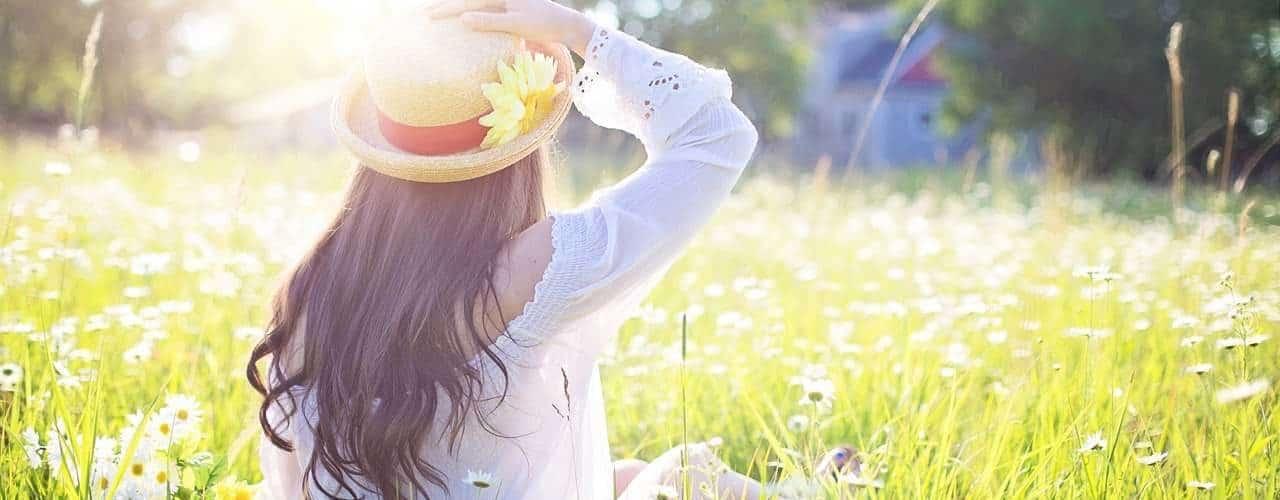 Femme portant un chapeau vue de dos dans l'herbe